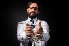 Wzburzony w średnim wieku biznesmen w eyeglasses stać wiązał z arkaną obrazy royalty free