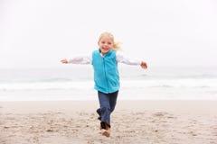 wzdłuż plażowej dziewczyny wakacyjnych działających zima potomstw zdjęcia royalty free