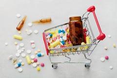 Wózek na zakupy pełno farmaceutyczne leka i medycyny pigułki Fotografia Stock