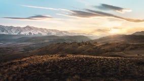 Wzgórza i śnieżne góry przy zmierzchem Fotografia Stock