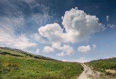 Wzgórze krajobraz z głębokim niebieskim niebem i dużą chmurą Obraz Royalty Free