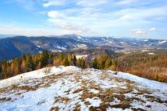 Wzgórze zakrywający w śniegu przeciw pasmu górskiemu Fotografia Stock