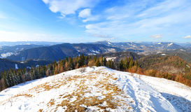 Wzgórze zakrywający w śniegu przeciw pasmu górskiemu Fotografia Royalty Free