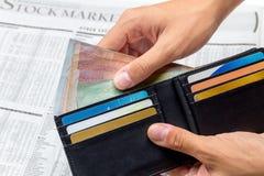 Wziąć pieniądze z kieszeni nad rynek papierów wartościowych gazetą Obraz Royalty Free