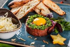 Wzmacnia tartare słuzyć z jajecznym yolk, siekać zielonymi cebulami, grzanką i masłem w talerzu na zmroku kamienia tle, Czyści ła zdjęcia stock