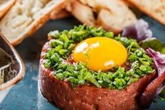 Wzmacnia tartare słuzyć z jajecznym yolk, siekać zielonymi cebulami, grzanką i masłem w talerzu na zmroku kamienia tle, Czyści ła fotografia royalty free