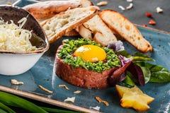 Wzmacnia tartare słuzyć z jajecznym yolk, siekać zielonymi cebulami, grzanką i masłem w talerzu na zmroku kamienia tle, Czyści ła obraz stock