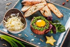 Wzmacnia tartare słuzyć z jajecznym yolk, siekać zielonymi cebulami, grzanką i masłem w talerzu na zmroku kamienia tle, Czyści ła zdjęcie stock