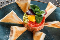 Wzmacnia tartare słuzyć z jajecznym yolk, siekającym avocado, pomidorami i grzanką w talerzu na zmroku kamienia tle, Czyści łasow obraz royalty free