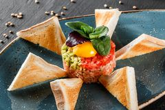 Wzmacnia tartare słuzyć z jajecznym yolk, siekającym avocado, pomidorami i grzanką w talerzu na zmroku kamienia tle, Czyści łasow zdjęcia royalty free