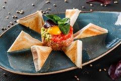 Wzmacnia tartare słuzyć z jajecznym yolk, siekającym avocado, pomidorami i grzanką w talerzu na zmroku kamienia tle, Czyści łasow zdjęcia stock