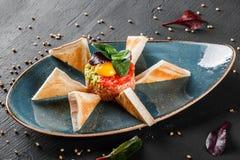 Wzmacnia tartare słuzyć z jajecznym yolk, siekającym avocado, pomidorami i grzanką w talerzu na zmroku kamienia tle, Czyści łasow obraz stock
