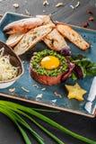 Wzmacnia tartare s?uzy? z jajecznym yolk, sieka? zielonymi cebulami, grzank? i mas?em w talerzu na zmroku kamienia tle, Czy?ci ?a obrazy stock