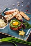 Wzmacnia tartare s?uzy? z jajecznym yolk, sieka? zielonymi cebulami, grzank? i mas?em w talerzu na zmroku kamienia tle, Czy?ci ?a obraz stock