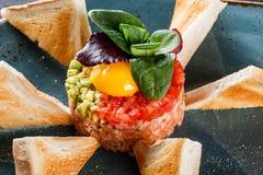 Wzmacnia tartare s?uzy? z jajecznym yolk, siekaj?cym avocado, pomidorami i grzank? w talerzu na zmroku kamienia tle, Czy?ci ?asow obraz stock