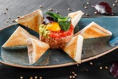 Wzmacnia tartare s?uzy? z jajecznym yolk, siekaj?cym avocado, pomidorami i grzank? w talerzu na zmroku kamienia tle, Czy?ci ?asow zdjęcie royalty free