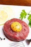 Wzmacnia tartare z jajecznym yolk na drewnianym stołu i bielu talerzu zdjęcia royalty free