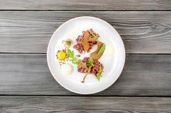 Wzmacnia winnika surowa minced mięsna restauracja słuzyć na białym dużym talerzu, szary drewniany tło, przestrzeń dla teksta menu Obrazy Stock