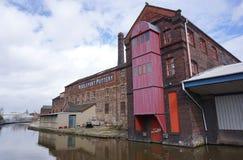 Wznawiający fabryczni i przemysłowi budynki obok kanału, na Zdjęcie Royalty Free