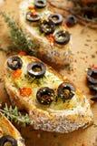 Wznoszący toast baguette z serem, blck oliwkami, chili pieprzem i macierzanką, Zdjęcie Stock
