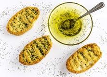 Wznoszący toast chleb z ziele i oliwą z oliwek na wznoszącym toast czosnku chlebie Biały tło zdjęcie stock