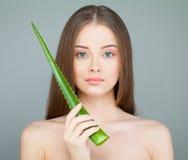 Wzorcowa kobieta z Śliczną twarzą, Świeżą skórą i zieleń aloesu liściem, fotografia stock