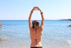Wzorcowa reklamowa grecka biżuteria na plaży - tworzący kierowego symbol z ona ręki Zdjęcie Stock