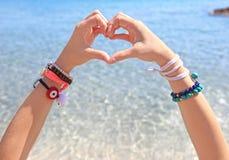 Wzorcowa reklamowa grecka biżuteria na plaży - tworzący kierowego symbol z ona ręki Obrazy Royalty Free