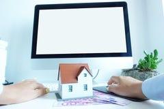 Wzorcowy dom przed komputerem z pustym bielu ekranem jako tło, stoi na gotówkowych banknotach Nieruchomości online transac Fotografia Stock