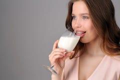 Wzorcowy oblizania mleko od wina szkła z bliska Szary tło Obraz Stock