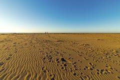 Wzorzystość Plażowy piasek z odcisku stopy niebieskiego nieba Nabrzeżnym krajobrazem Obraz Stock