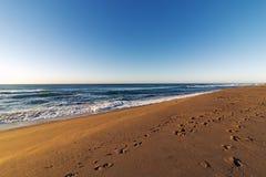 Wzorzystość Plażowy piasek z odcisku stopy niebieskiego nieba Nabrzeżnym krajobrazem Fotografia Stock