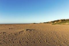 Wzorzystość Plażowy piasek z odcisku stopy niebieskiego nieba Nabrzeżnym krajobrazem Obraz Royalty Free