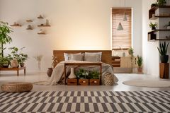 Wzorzysty dywan przed łóżkiem w botanicznym sypialni wnętrzu z roślinami i okno Istna fotografia obrazy stock