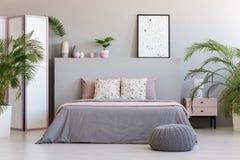 Wzorzysty plakat na popielatym headboard łóżko z poduszkami w bedroo fotografia stock