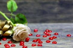 Wzrastał kwiatu i małych czerwonych serc rozpraszających na drewnianym stole Obrazy Stock