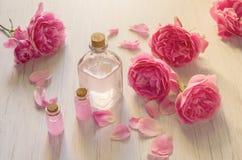 Wzrastał wodę w szklanych butelkach i menchii róża kwitnie na drewnianym lekkim tle obrazy stock