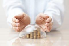 Wzrastający monety ochraniać pod szklaną kopułą i rękami zdjęcia stock