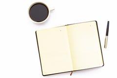 A xícara de café, abre o diário e a pena em um fundo branco Conceito mínimo do negócio do lugar de funcionamento no escritório foto de stock royalty free