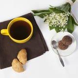 Xícara de café amarela, um ramalhete dos lírios do vale, um bloco de notas para notas e uns pires com as duas cookies da brownie  Fotos de Stock