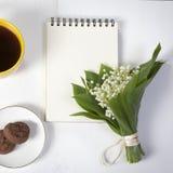 Xícara de café amarela, um ramalhete dos lírios do vale, um bloco de notas para notas e uns pires com as duas cookies da brownie  Imagem de Stock