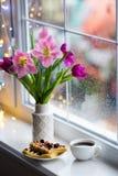 A xícara de café, as bolachas com bagas e o vaso branco com o ramalhete macio de tulipas cor-de-rosa bonitas aproximam a janela c Imagem de Stock
