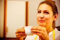 Xícara de café bebendo da mulher madura na cozinha Fotografia de Stock Royalty Free