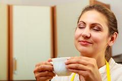 Xícara de café bebendo da mulher madura na cozinha Fotografia de Stock