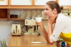 Xícara de café bebendo da mulher madura na cozinha Imagens de Stock Royalty Free