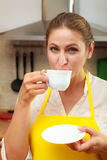 Xícara de café bebendo da mulher madura na cozinha Imagens de Stock