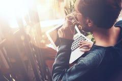 Xícara de café bebendo do homem e trabalho com portátil O portátil genérico do projeto está em seus joelhos Efeitos de Sunlights fotografia de stock