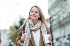 X?cara de caf? bonita da terra arrendada da jovem mulher ao andar na rua fotografia de stock royalty free