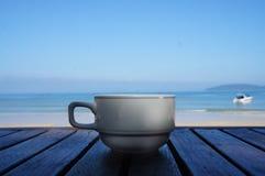 Xícara de café branca da porcelana no fundo do mar fotografia de stock