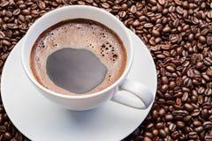 Xícara de café branca em feijões de café imagem de stock